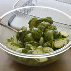 Use a large mixing bowl to toss your Brussels sprouts with olive oil, salt