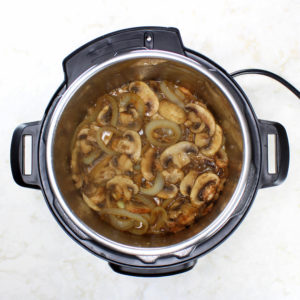 Stir in the onions and mushrooms.