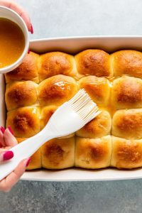 While the tops are still hot, brush them with melted or softened butter.
